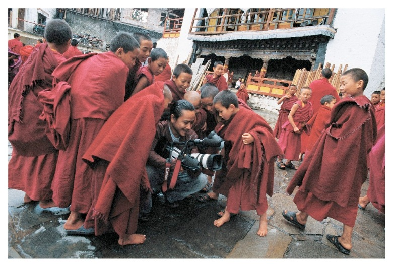 Surrounded by young monks, Moji Riba films rituals celebrating Buddha's birth at Galden Namgyal Lhatse monastery. Tawang, Arunachal Pradesh, India, 2008 (Photo courtesy Rolex Awards)