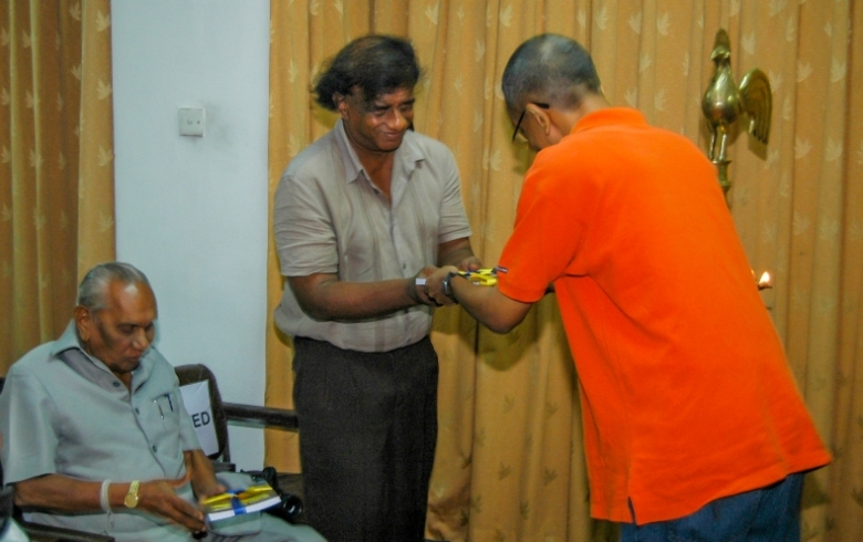 Nalaka presenting book to his science teacher & first publisher, Asanga Abeysundara