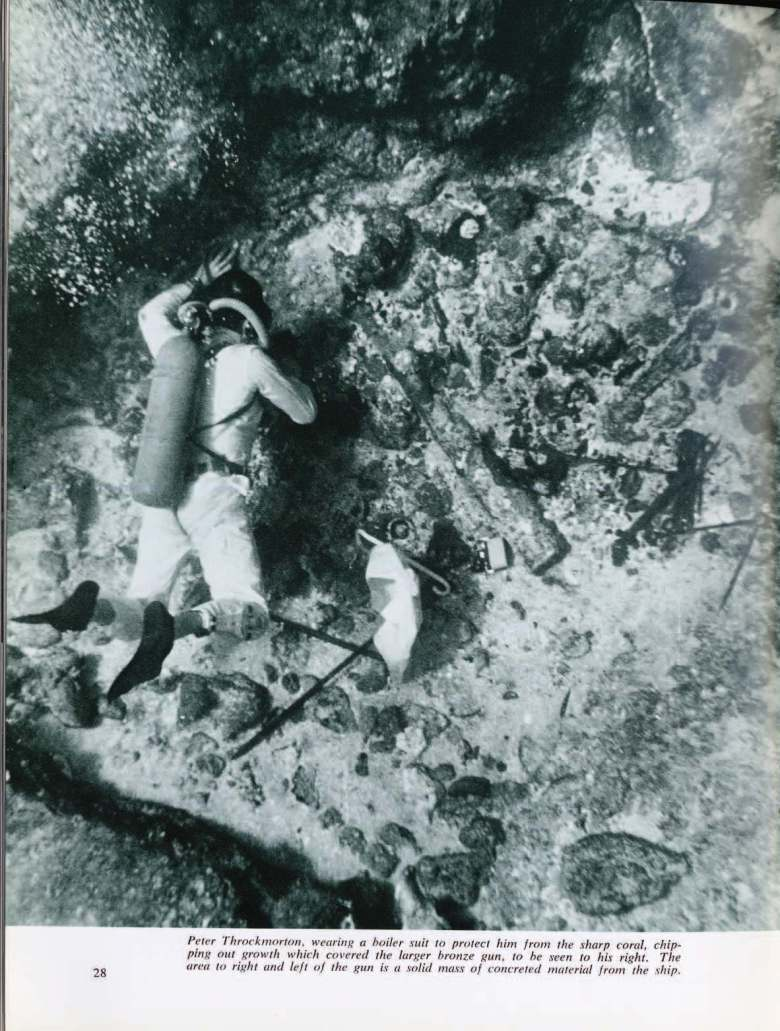 Peter Throckmorton, wearing a boiler suit to protect him from the sharp coral, chipping out growth which covered the larger bronze gun, to his right.