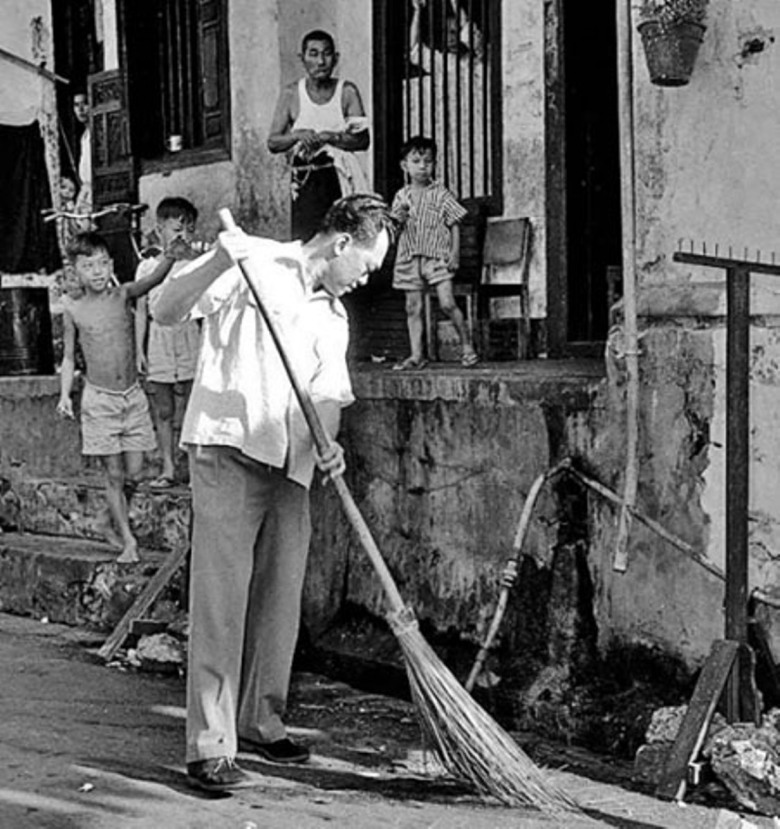 Lee is seen sweeping the streets during a mass clean-up campaign in Singapore, 1959