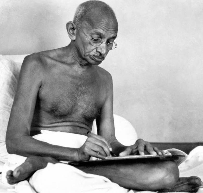 Mahatma Gandhi writing an article