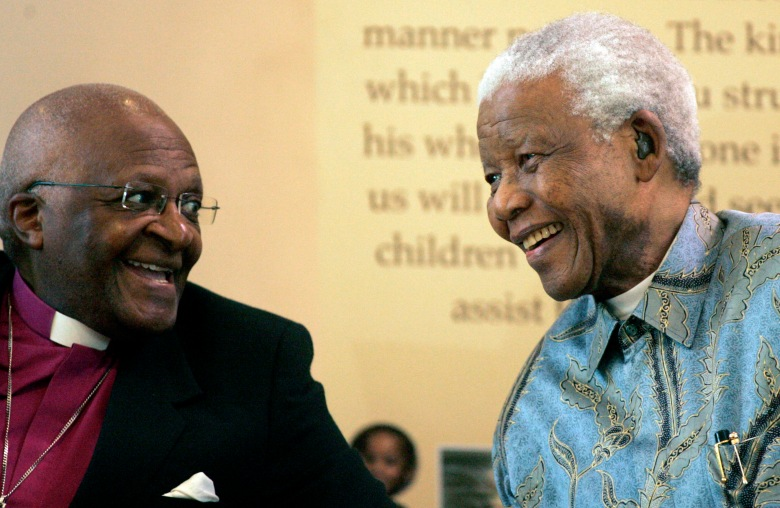 Former South African President Nelson Mandela, right, reacts with Archbishop Desmond Tutu, left, during the launch of a Walter and Albertina Sisulu exhibition, called, 'Parenting a Nation', at the Nelson Mandela Foundation in Johannesburg, South Africa, on 12 March 2008 (AP Photo/Themba Hadebe)
