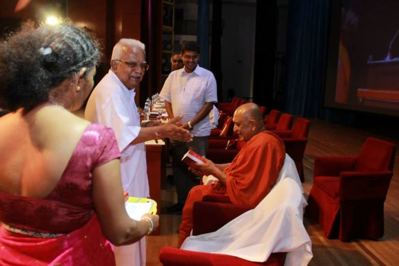 Sarvodaya leader Dr A T Ariyaratne presenting his autobiography to Ven Sobitha at BMICH on 4 Aug 2014 (Sarvodaya photo)